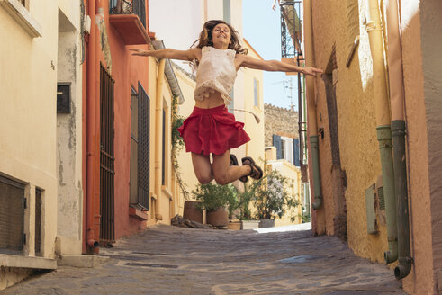 France, Collioure, young woman jumping in an alley - SKCF00314