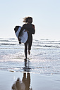 Portugal, Algarve, man running in the water with surfboard - JRF00323