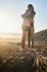 Portugal, Algarve, couple hugging at sunset on the beach - JRF00338