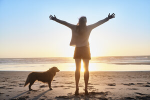 Portugal, Algarve, woman with dog raising arms on the beach at sunset - JRF00341