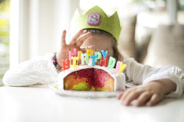 Girl hiding behind birthday cake - MOEF00130