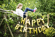 Decoration for Birthday Party in garden with golden balloons and swinging girl in the foreground - MOEF00133