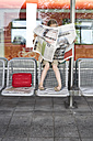 Little girl sitting at platform reading newspaper - FSF00948