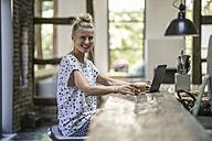 Woman sitting in kitchen, using laptop - RIBF00680