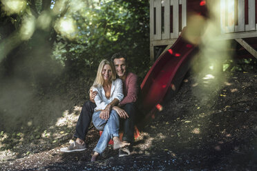 Happy couple sitting on slide of garden shed in the woods - RIBF00689