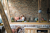 Mature woman sitting on couch, reading magazine - RIBF00695