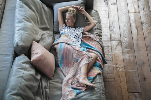 Woman relaxing on couch, wrapped in blanket - RIBF00713