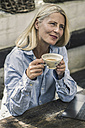 Mature woman sitting on terrace, drinking tea - RIBF00716
