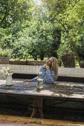 Mature woman sitting on terrace, enjoying summer - RIBF00725