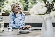 Mature woman sitting on terrace, with cherries on table - RIBF00728