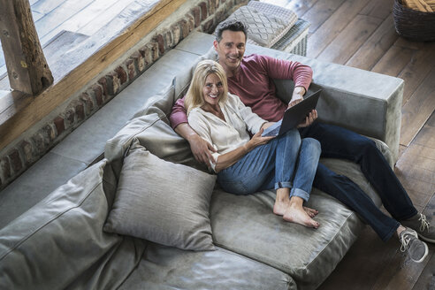 Couple sitting on couch, using laptop - RIBF00743