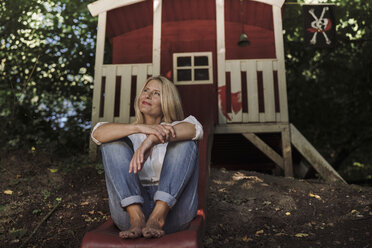 Mature woman sitting on slide in front of garden shed in the woods - RIBF00746
