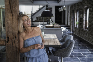 Woman standing in her comfortable country house, smiling - RIBF00761