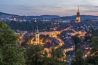 Switzerland, Bern, cityscape with lighted Nydeggkirche and minster at evening twilight - KEBF00621