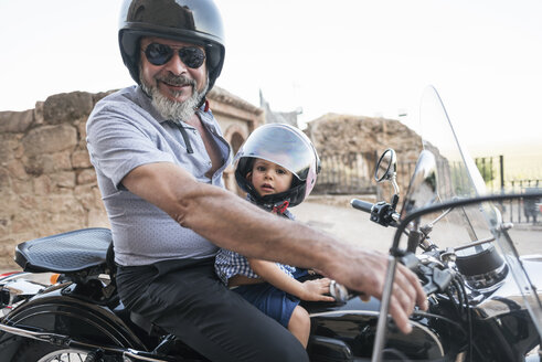 Spain, Jaen, grandfather with grandson on motorcycle with a sidecar - JASF01825
