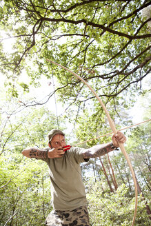 Man shooting with bow and arrow in the forest - MFRF00985