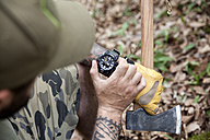 Close-up of man with axe in forest checking the time - MFRF00997