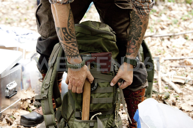 Man with axe and backpack in forest - MFRF01003