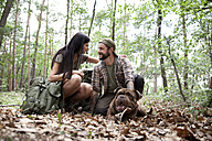 Couple with backpack and dog in forest - MFRF01006