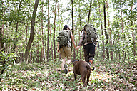 Couple with backpacks and dog on a hiking trip in forest - MFRF01009