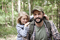 Portrait of smiling father and daughter in forest - MFRF01015