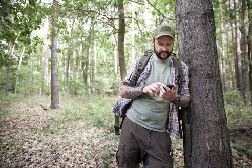 Man with backpack on a hiking trip in forest using cell phone - MFRF01018