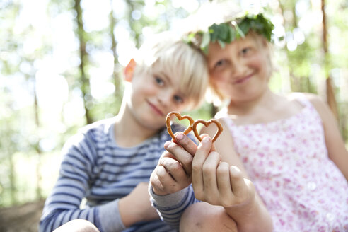 Boy and girl in forest holding heart-shaped pretzel pastry - MFRF01027