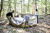 Family in forest building up tent together - MFRF01030