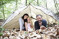Portrait of happy family with daughter in tent in forest - MFRF01033