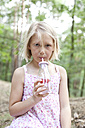 Girl drinking from glass of infused water in forest - MFRF01036