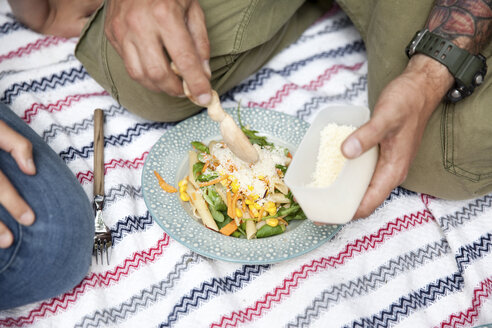 Man dispersing grated cheese on pasta salad during a picnic - MFRF01039