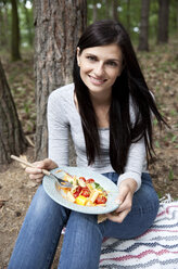 Portrait of smiling woman eating pasta salad during a picnic in forest - MFRF01042