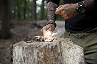 Man igniting a fire on tree stump in the forest - MFRF01045