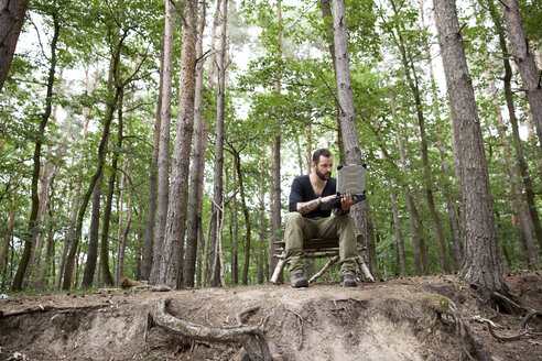 Man sitting on self-made wooden chair in forest using laptop - MFRF01048