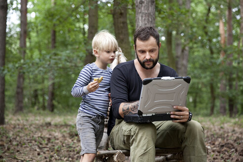 Father and son sitting on self-made wooden chair in forest using laptop - MFRF01051