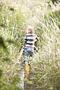 Girl with rubber boots wading in brook - MFRF01060