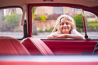 Portrait of smilng blond girl leaning on car window looking inside - SIPF01691