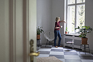 Mature woman at home looking out of window - RBF05849