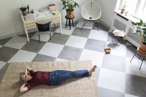 Relaxed mature woman lying on the floor at home - RBF05852