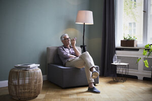 Mature man using cell phone at home - RBF05867