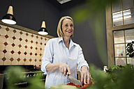 Smiling mature woman chopping bell pepper in kitchen - RBF05879