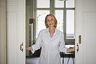 Portait of smiling mature woman opening door at home - RBF05882