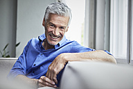 Portrait of smiling mature man sitting on couch at home - RBF05897