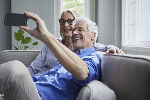 Happy mature couple sitting on couch at home taking a selfie - RBF05900