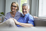 Portrait of smiling mature couple on couch at home - RBF05903