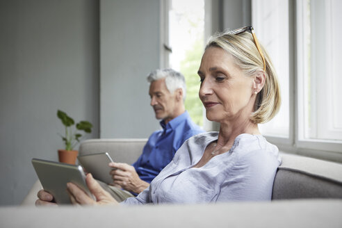 Mature couple sitting on couch at home using tablets - RBF05906