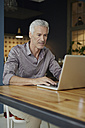 Mature man using laptop on table at home - RBF05924