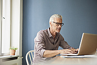 Mature man using laptop on table at home - RBF05927