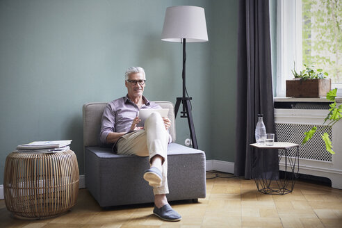 Portrait of smiling mature man using tablet at home - RBF05933
