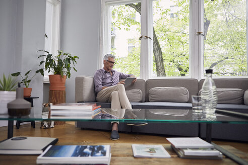 Mature man using tablet on couch at home - RBF05939